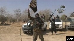 A video grab shows the leader of the Islamist extremist group Boko Haram, Abubakar Shekau, holding up a flag as he delivers a message.