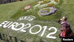 Kiyevdə Avropa Çempionatının rəsmi loqosu çəkilən çəməndə şəkil çəkdirən qadın, 8 iyun 2010