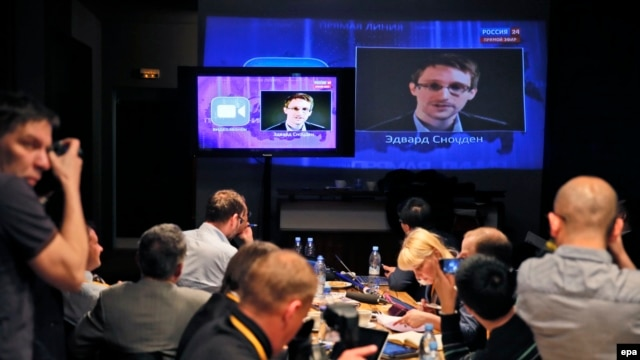 Journalists in Moscow listen to a speech and a question posed by former NSA contractor Edward Snowden at a media center during Russian President Vladimir Putin's nationwide phone-in program in April 2014.