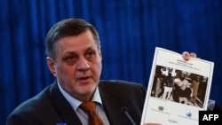 UN Special Representative to Afghanistan Jan Kubis holds up a copy of a report on civilian casualties at a press conference in Kabul on February 8, 2014.
