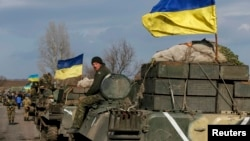 A convoy of Ukrainian armed forces, including armored personnel carriers, military vehicles, and cannons, prepares to move as the troops pull back from the Debaltseve region, in Blahodatne, on February 27.