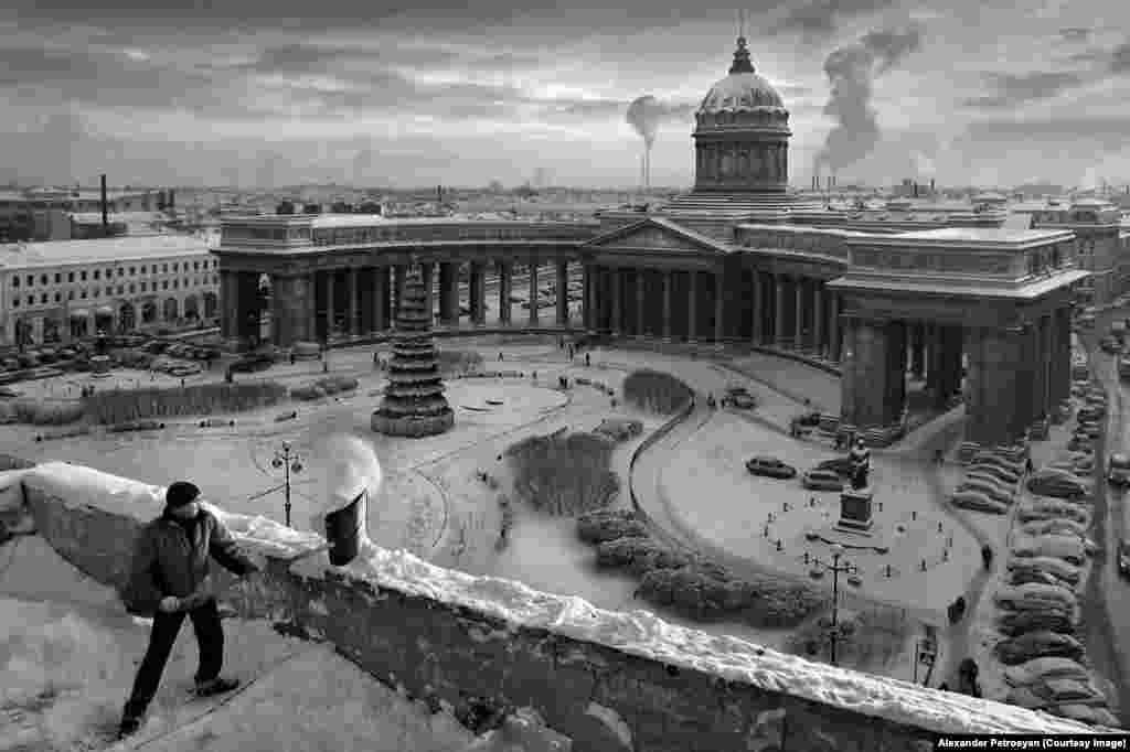 A worker clearing snow from a rooftop opposite Kazan Cathedral.