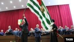 Рауль Хаджимба держит в руках флаг Абхазии во время церемонии инаугурации после победы на президентских выборах в 2014 году.