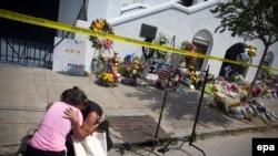 Две плачущие женщины перед мемориальным участком у Методистской епископиальной церкви в Чарлстоне, где девять человек были убиты
