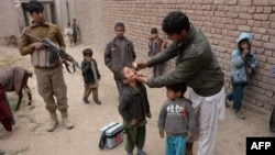 An Afghan policeman stands guard as a health worker administers polio drops to a child during a polio vaccination campaign on the outskirts of Jalalabad on January 26.