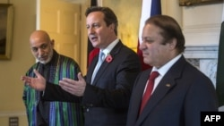 British Prime Minister David Cameron (center), Afghan President Hamid Karzai (left) and Pakistani Premier Nawaz Sharif (right) pose for pictures ahead of their trilateral meeting in Downing Street, London, on October 29.