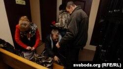 Супрацоўнікі спэцслужбаў даглядаюць людзей перад пачаткам паседажньня на працэсе Кавалёва-Канавалава