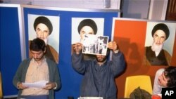 Iranian student spokesmen hold up photos of blindfolded American hostages, during a press conference in Tehran Monday November 5, 1979. The hostages are members of the staff of the United States Embassy in Tehran, which was stormed by students November 4