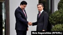 """Грузия президенті Михаил Саакашвили (сол жақта) """"Грузия арманы"""" коалициясының жетекшісі Бидзина Иванишвилиді парламент сайлауындағы жеңісімен құттықтап тұр. Тбилиси, 9 қазан 2012 жыл."""