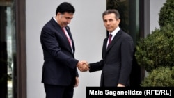 Грузия президенті Михаил Саакашвили (сол жақта) оппозиция жетекшісі Бидзина Иванишвилиді жеңісімен құттықтап тұр. Тбилиси, 9 қазан 2012 жыл.