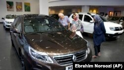 In this July 16, 2015 photo, Iranians look at a Renault sedan at a dealership in northern Tehran, Iran.