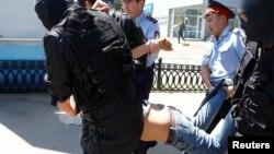 Полицейские тащат задержанного, который пришел к центральной площади, где намечался протест против инициированной правительством земельной реформы. Алматы, 21 мая 2016 года.
