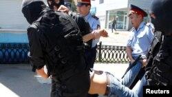 Полицейские тащат парня недалеко от площади Республики в Алматы. 21 мая 2016 года.