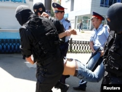 Kazakh riot police officers detain a demonstrator during a protest against land reforms in May 2016.