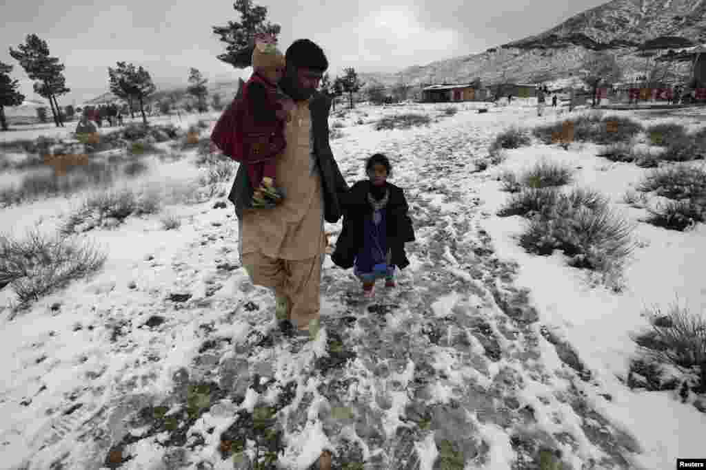 A man and his daughters walk along Hanna Lake after a snowfall on the outskirts of Quetta, Pakistan. (Reuters/Naseer Ahmed)