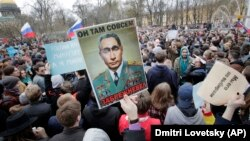 Protesters carry a poster depicting President Vladimir Putin as an elderly Soviet leader in St. Petersburg on May 5.