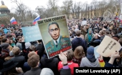 Anti-Putin demonstrators carry a poster drawing a comparison between the Russian president and the elderly Soviet Communist leader Leonid Brezhnev during a protest rally in St. Petersburg on May 5.