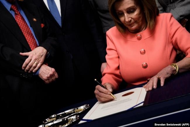 Udhëheqësja e Dhomës së Përfaqësuesve, Nancy Pelosi duke nënshkruar artikujt për shkarkim të Trumpit.