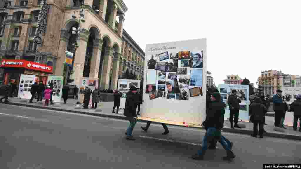 Люди беруть щити із фотографіями Героїв Небесної сотні й несуть на дорогу