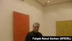 الفنان العراقيمدحت كاكائي امام لوحتين من اعماله