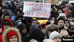 "Protesters rally against the law banning Americans from adopting Russian children in St. Petersburg on January 13. The sign reads, ""Murderers of children, get out of the Duma."""