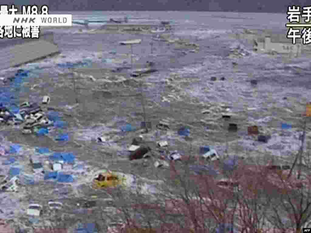 Japan--screen grab shows cars and containers floating in a massive tsunami wave to have hit Sendai, 11Mar2011 - Скриншот выпуска новостей телекомпании NHK 11 марта 2011. Вагоны и контейнеры плавают в волне цунами. JAPAN OUT AFP PHOTO / HO / NHK