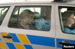 Jana Nagyova sits in a police car after being arrested for abuse of power and bribery.