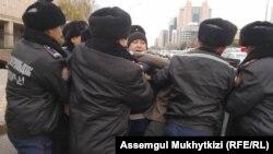 Полицейлердің белсенді Дулат Ағаділді (ортада) күштеп ұстап жатқан сәті. Нұр-Сұлтан, 26 қазан 2019 жыл.