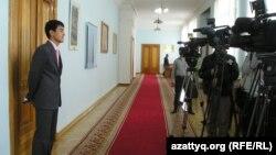 Чиновник стоит перед камерами казахстанских телеканалов. Иллюстративное фото.
