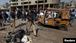 A policeman instructs people to move away from the site of an explosion in Karachi on April 25, 2014