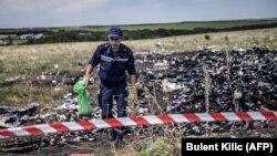 Сотрудник МЧС Украины на месте падения обломков самолета компании Malaysia Airlines. Донецкая область, 20 июля 2015 года.