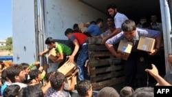 Banorët sirianë marrin ndihma nga një kamion, i cili ishte konfiskuar nga kryengritësit në një vendkalim me Turqinë afër qytetit Alepo, ditën e premte