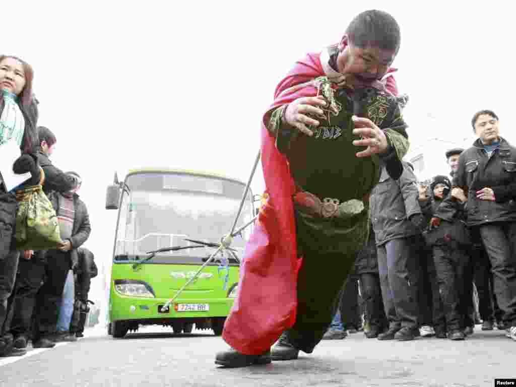 "Nurlan Alisherov, a 35-year-old unemployed man, tries to set a bus-pulling record for the ""Guinness Book Of World Records"" on Ala-Too square in Bishkek on November 28. (REUTERS/Vladimir Pirogov)"
