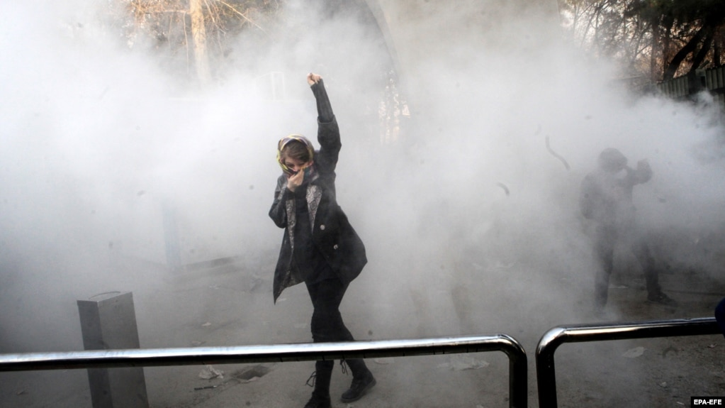 A young woman raises her fist aloft as Iranian students clash with riot police in Tehran during antigovernment protests that rocked Iran for around two weeks at the turn of the year.