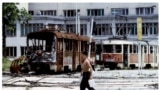 A Bosnian teenager carries containers of water in front of destroyed trams at Skenderia Square in Sarajevo on June 22, 1993. A woman passes through the same square on April 4, 2012.