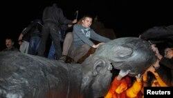 Участники акции взобрались на демонтированный памятник Ленину в центре Харькова в Украине. 28 сентября 2014 года.