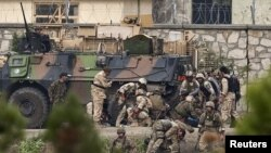 NATO and Afghan troops attend to casualties during the battle with Taliban insurgents who took over a building near the US Embassy in Kabul on September 13-14.