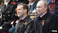 President Dmitry Medvedev (left) and Prime Minister Vladimir Putin watch the military parade in Moscow
