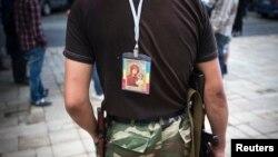 Сторонник ЛНР с иконой на спине охраняет административные здания в Луганске