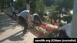 Сотрудники Андижанского областного управления юстиции убирают территорию возле здания своей конторы.