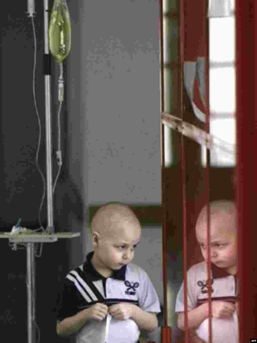 A child peers through a window at a children's hematological and oncological center in Minsk that was built after the Chornobyl nuclear accident. The scale of the health problems resulting from radiation remains difficult to assess.