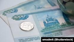 Монета номиналом 1 рубль и банкноты номиналом 1000 рублей.