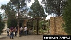 Люди стоят возле ворот офиса предпринимателя из Чиназского района Ташкентской области Ахмада Турсунбаева.