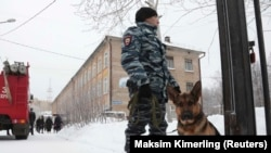 A police officer with a dog stands guard near the school in Perm on January 15.