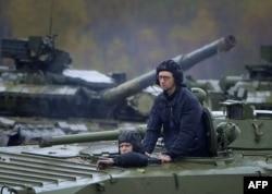 Прем'єр-міністр України Арсеній Яценюк стоїть у бронетранспортері під час візиту на військовому полігоні у районі Львова, 21 жовтня 2014 року