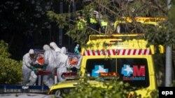 Медики в специальных защитных костюмах перевозят пациента с подозрением на лихорадку Эбола.
