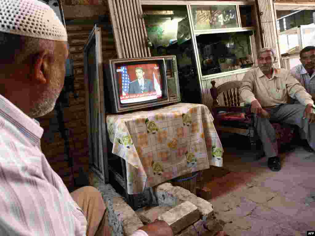 "IRAQ, Baghdad : Iraqi men watch a live broadcast on satellite television of a speech delivered in Cairo by US President Barrack Obama in Baghdad on June 4, 2009. President Barack Obama today vowed to forge a ""new beginning"" for Islam and America in a landmark speech to global Muslims, evoking a vision of peace after smouldering years of ""suspicion and discord."""