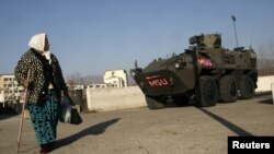 A woman passes by an Austrian KFOR armored vehicle guarding the main bridge in the ethnically divided town of Mitrovica.