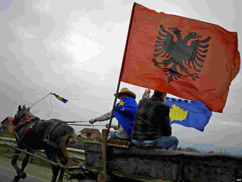 Kosovars fly the flags of Albania and Kosovo from a horse-drawn cart near the town of Mitrovica. - Kosovo on February 17 marked the second anniversary of its unilateral declaration of independence from Serbia. Photo by Armend Nimani for AFP