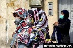 Люди в защитных масках на улицах Тегерана, 23 февраля 2020 года.